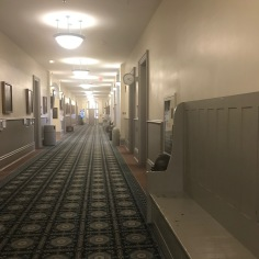 Corridor in the Old Main ; on the wall on the left, portraits of famous people connected to the building and to the Arkansas University at large